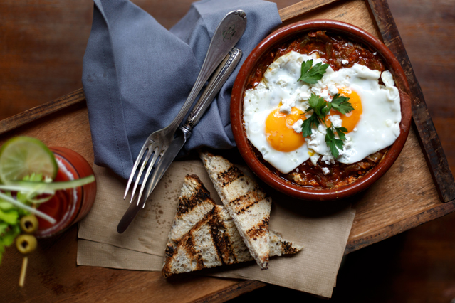 Shakshuka. A Tunisian inspired dish of baked eggs in a tomato, pepper & onion sauce with cumin, cayenne, feta, cilantro and bread